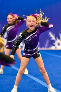 A cheerleader competes as part of a team at an ICE Extravaganza Cheer and Dance event