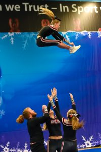 A coed cheer team compete a basket toss at ICE events
