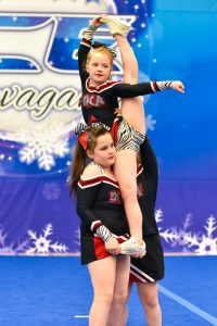 A cheer team dressed in black, red and white compete a stunt at an ICE competition
