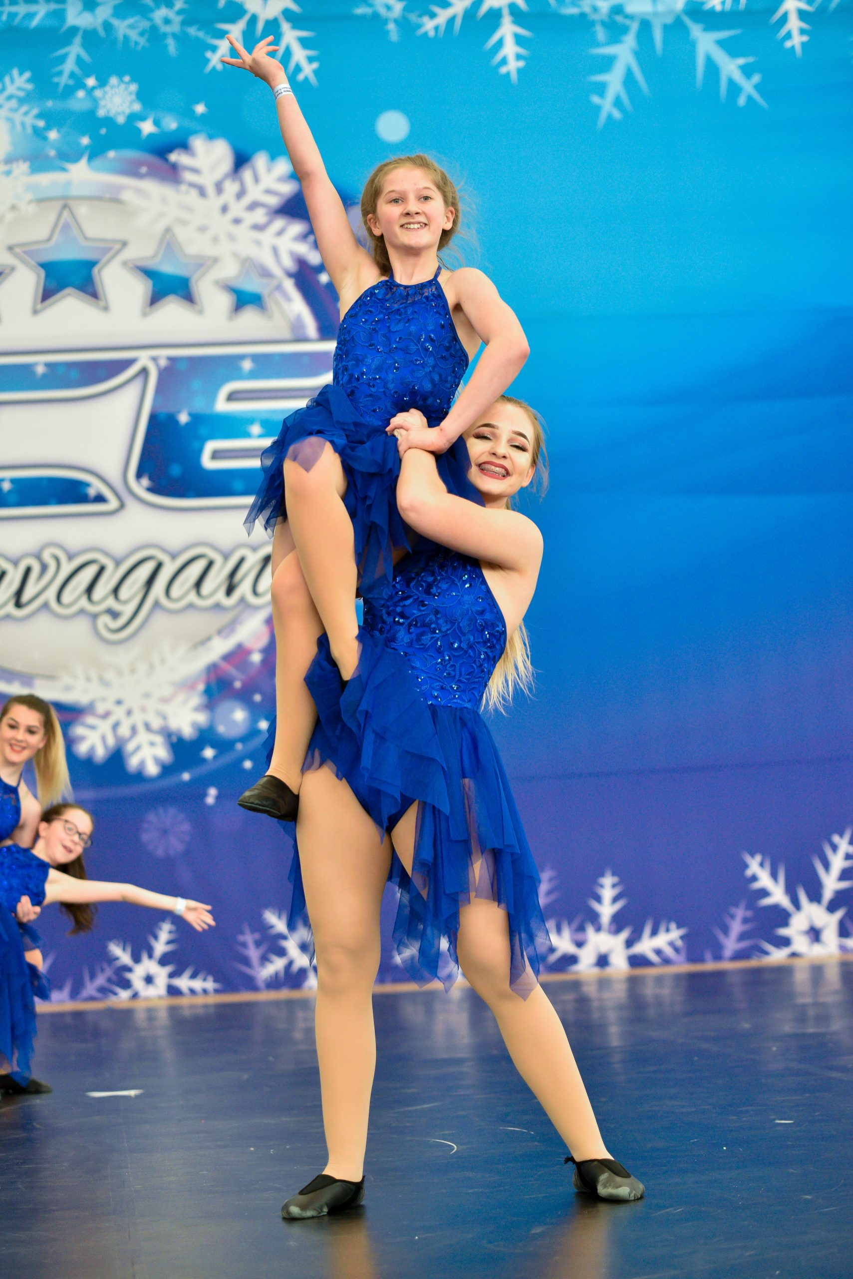 Dancers dressed in blue compete on a dance floor at ICE