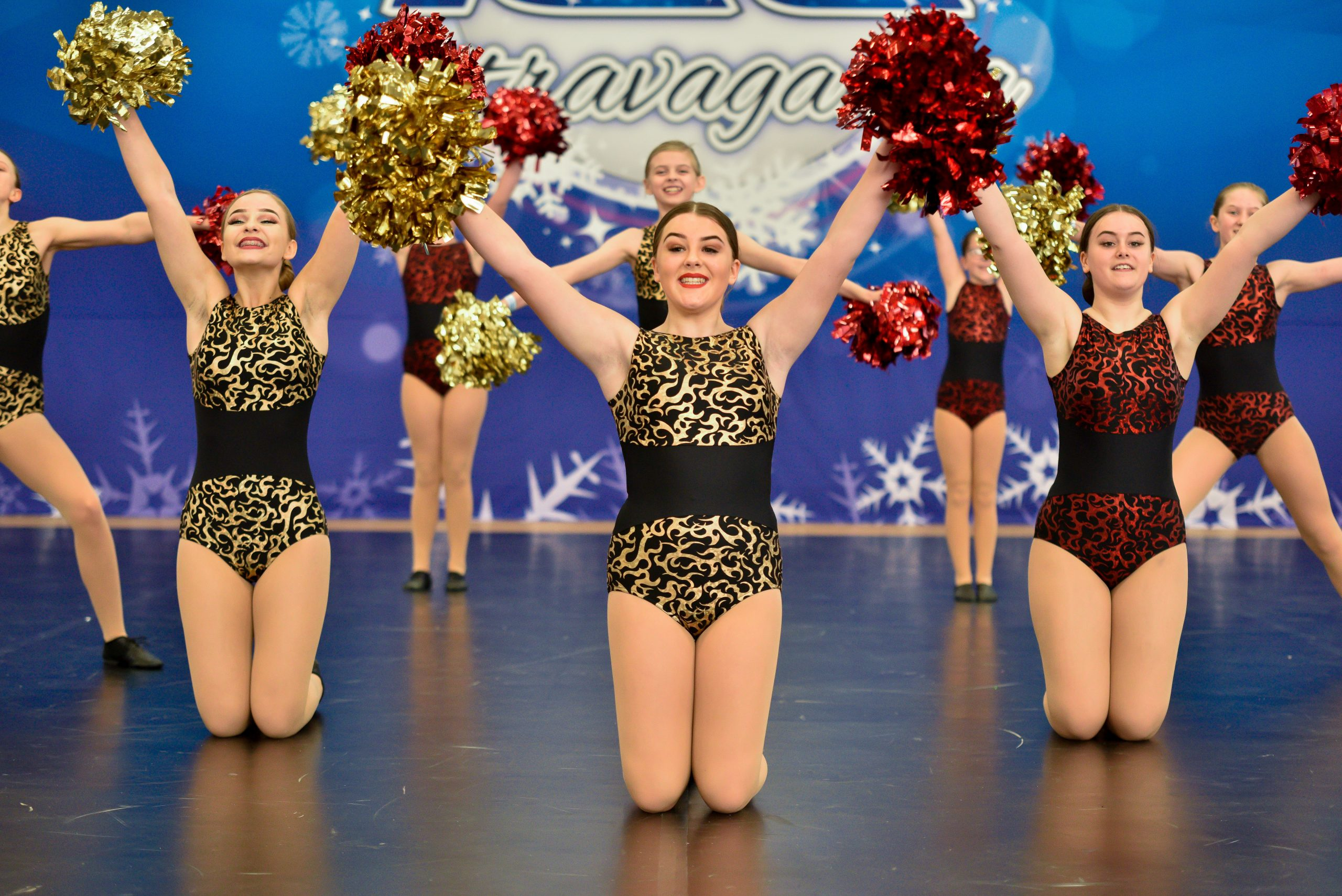 A pom team compete with red and gold poms on a dance floor at an ICE event