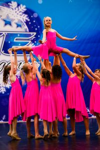 A dance team wearing pink compete on a dance floor at an ICE competition