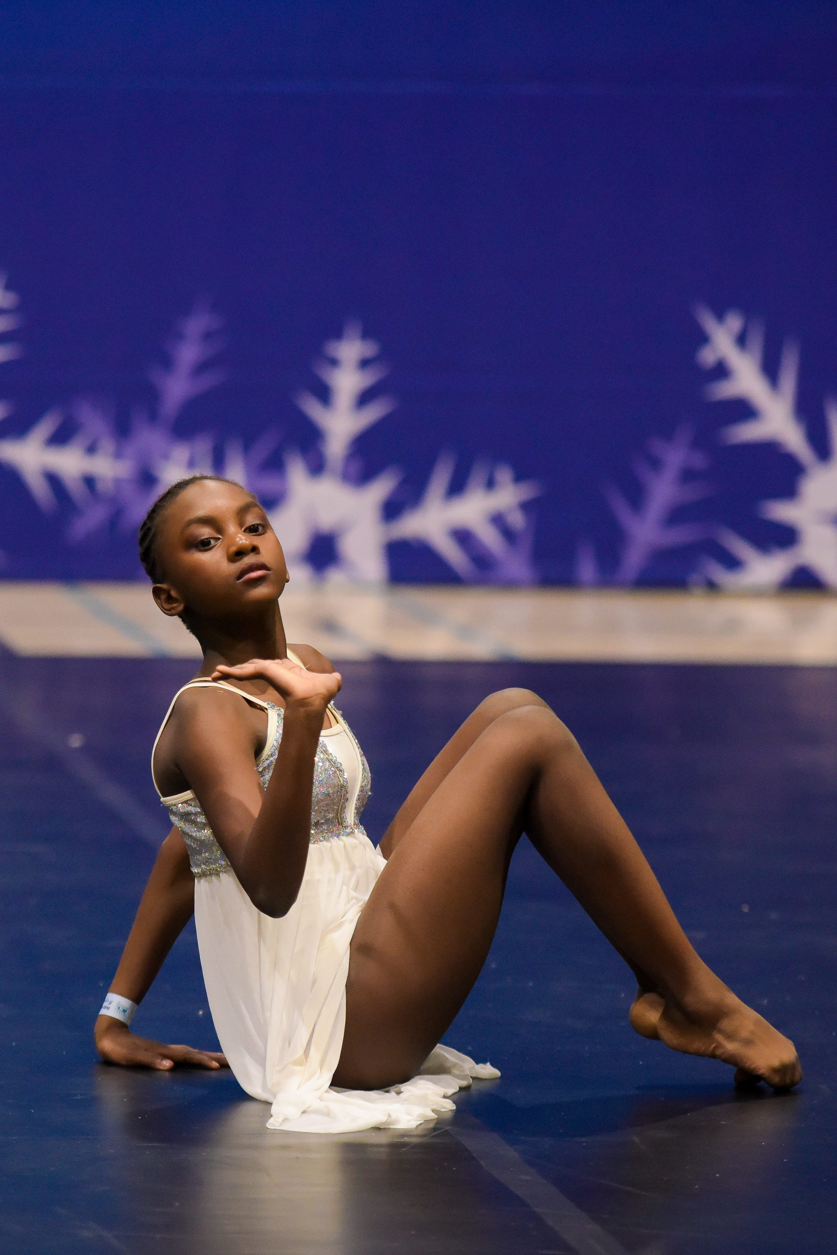 One dancer wearing a white dress performs floorwork at an ICE competition