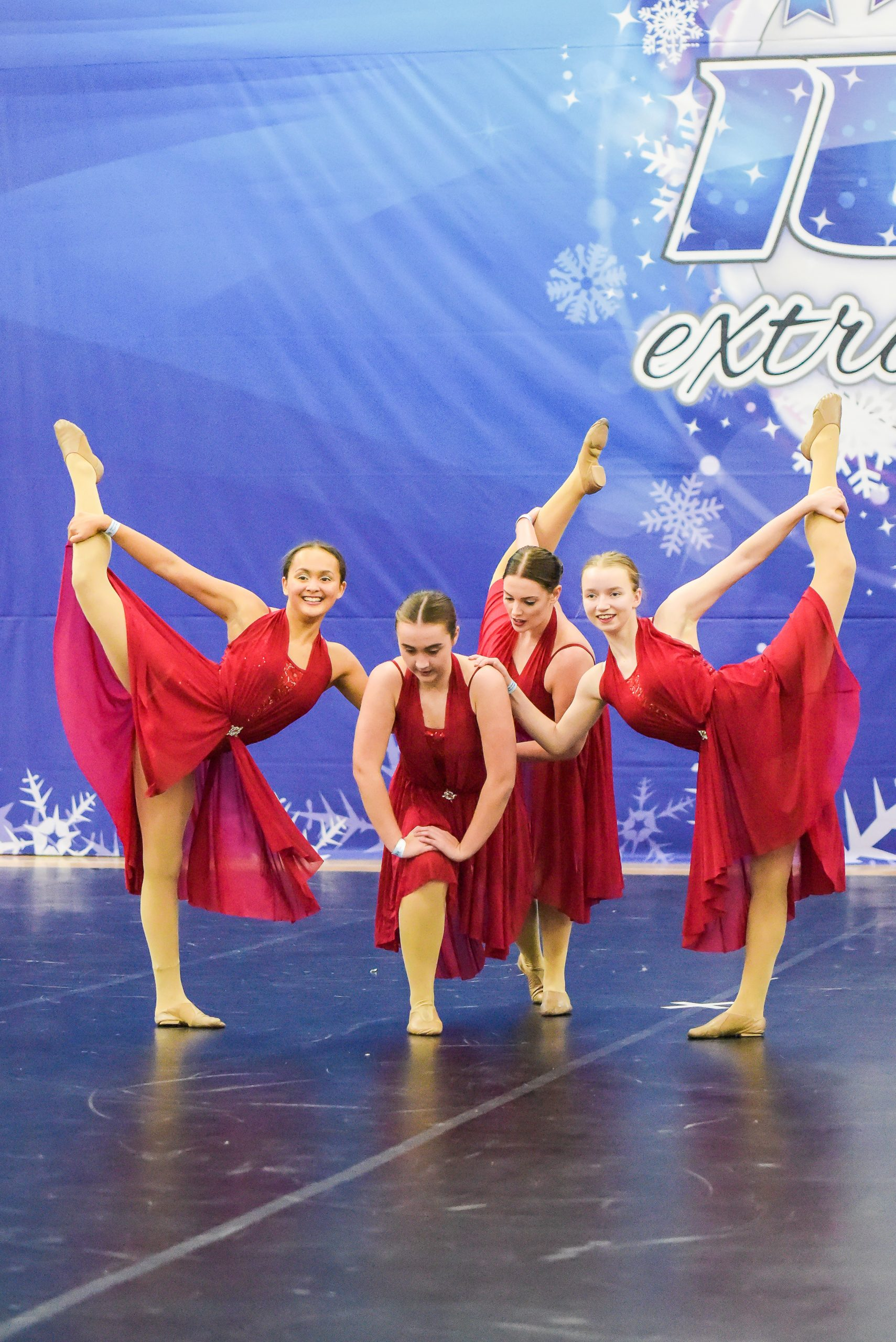 A dance team of four dancers wearing dresses compete at an ICE competition