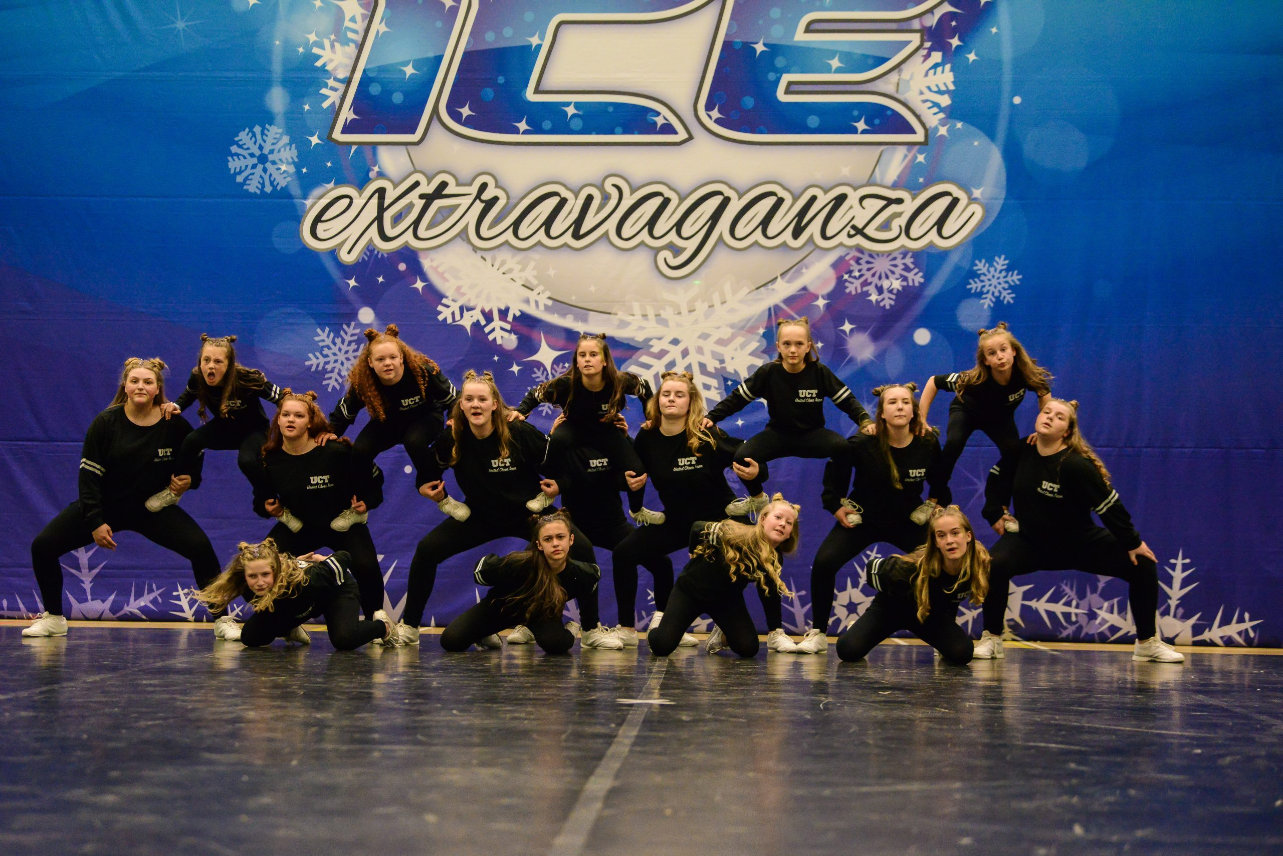 A hip hop dance team dressed in black compete on a dance floor at ICE