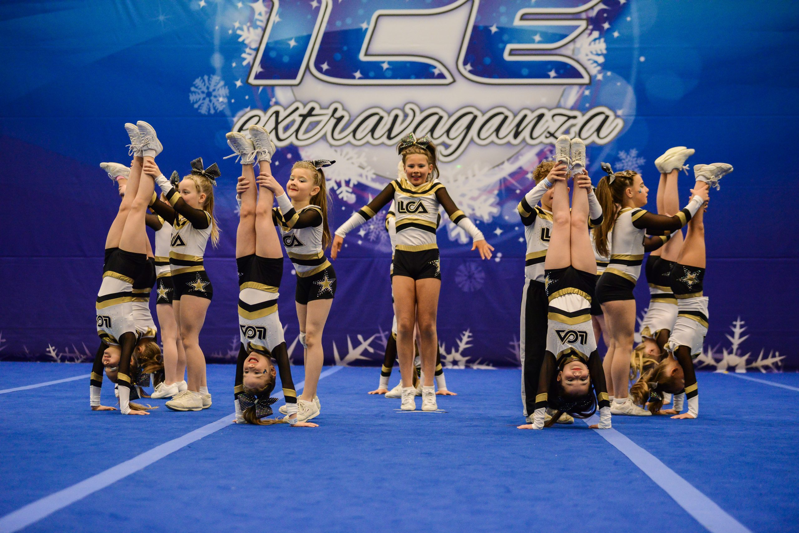 A cheer team in black, white and gold perform handstands