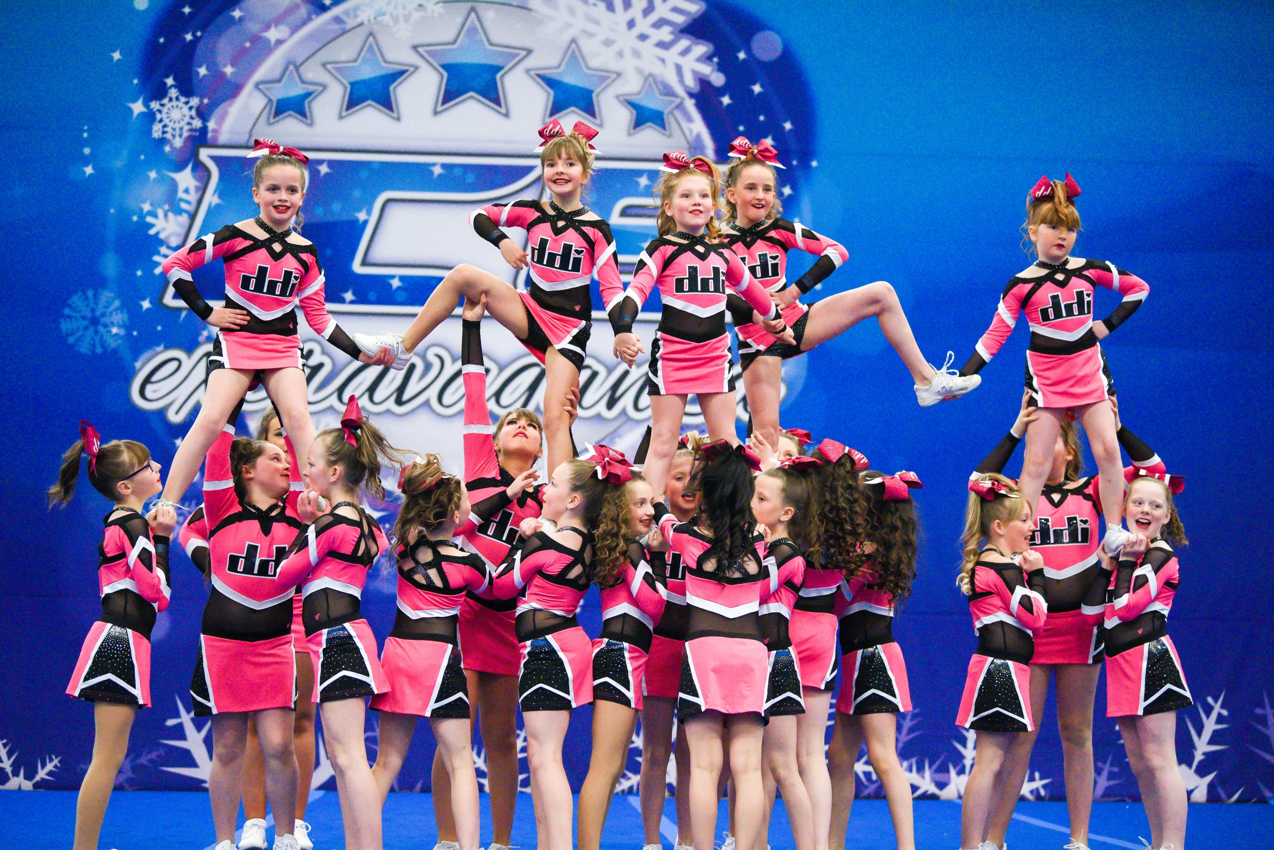 A cheer team dressed in pink and black perform a pyramid at an ICE Extravaganza competition