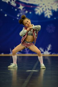 A hip hop soloist competes on a dance floor at an ICE competition