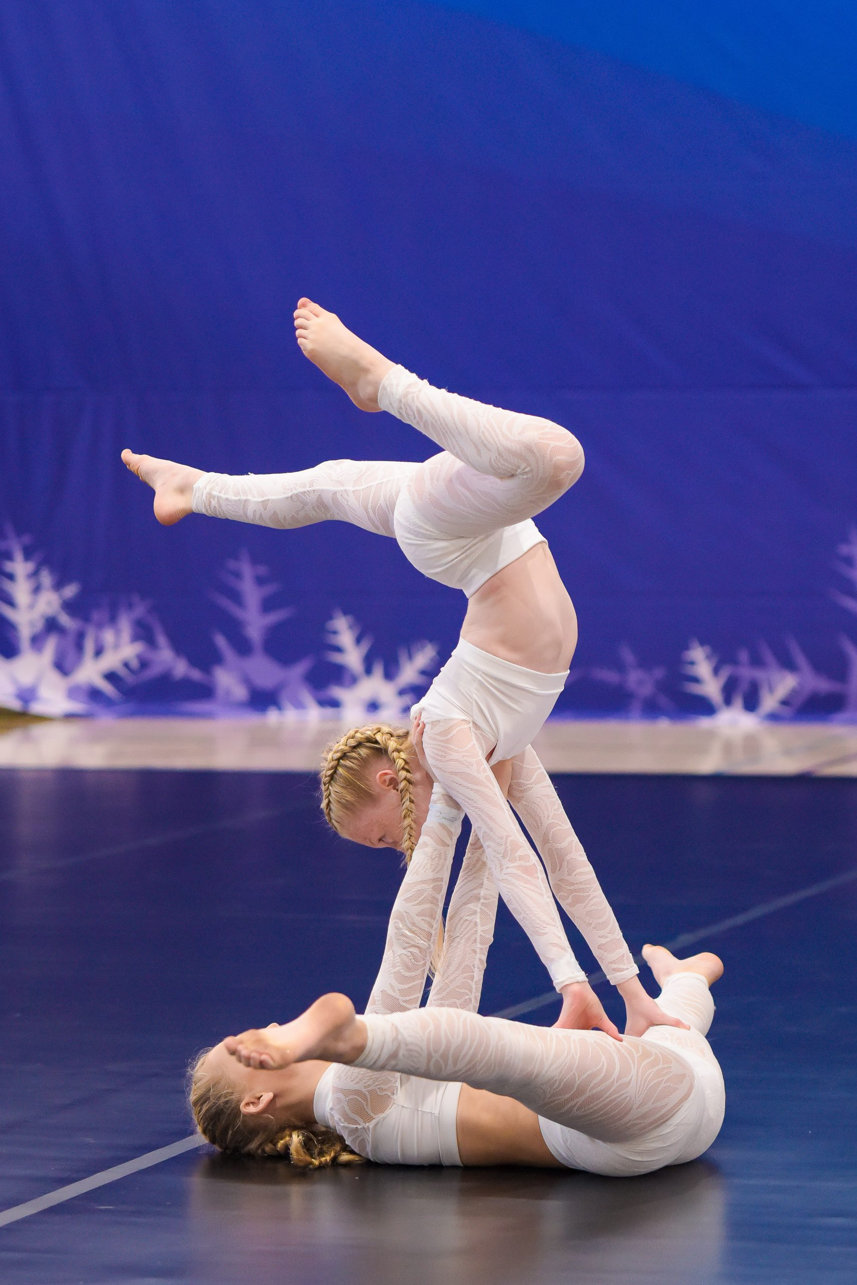 Two dancers dressed in white perform in an acro division at an ICE Ultimate Dance Experience event