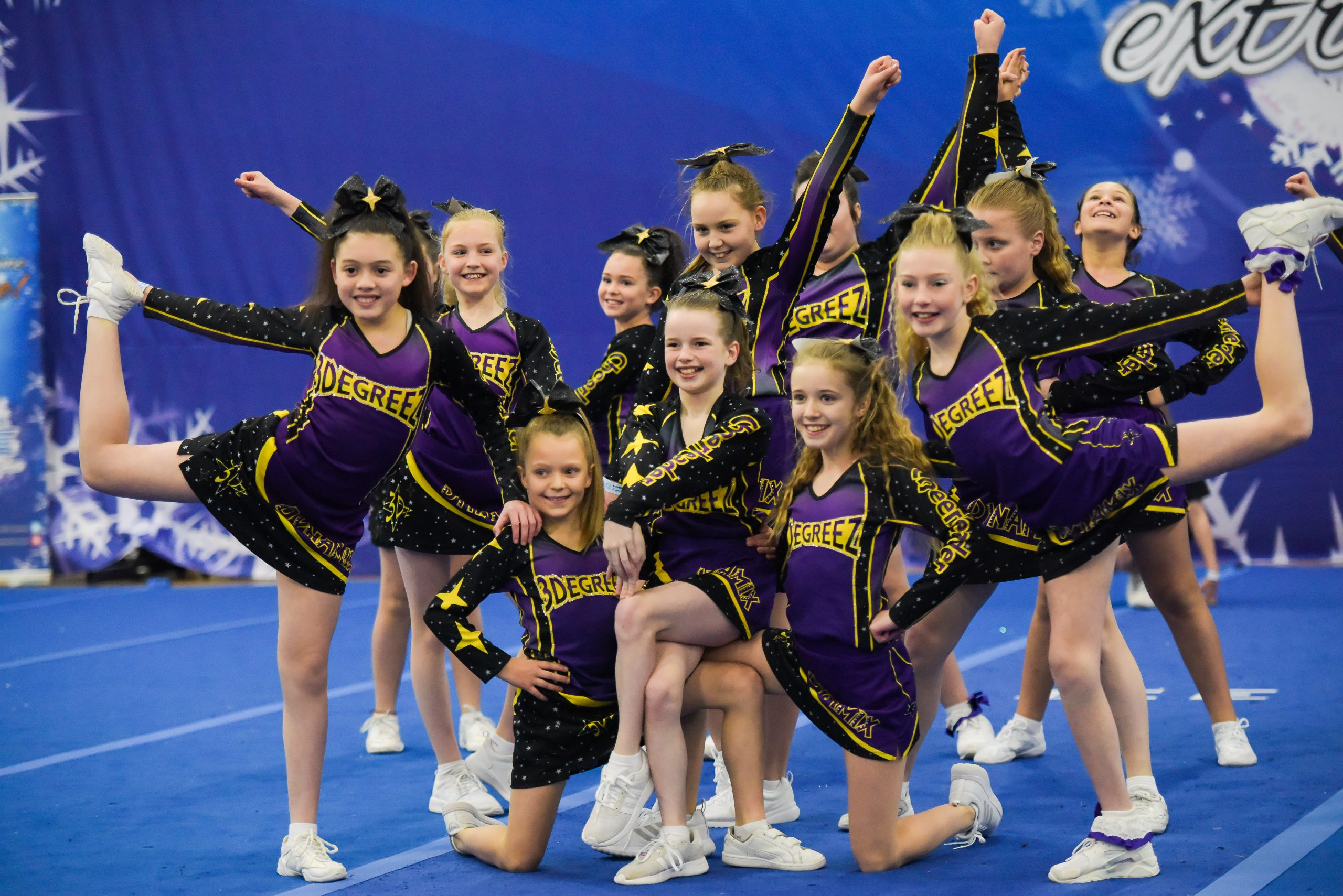 A cheer team wearing purple, black and yellow hit their end position at competition