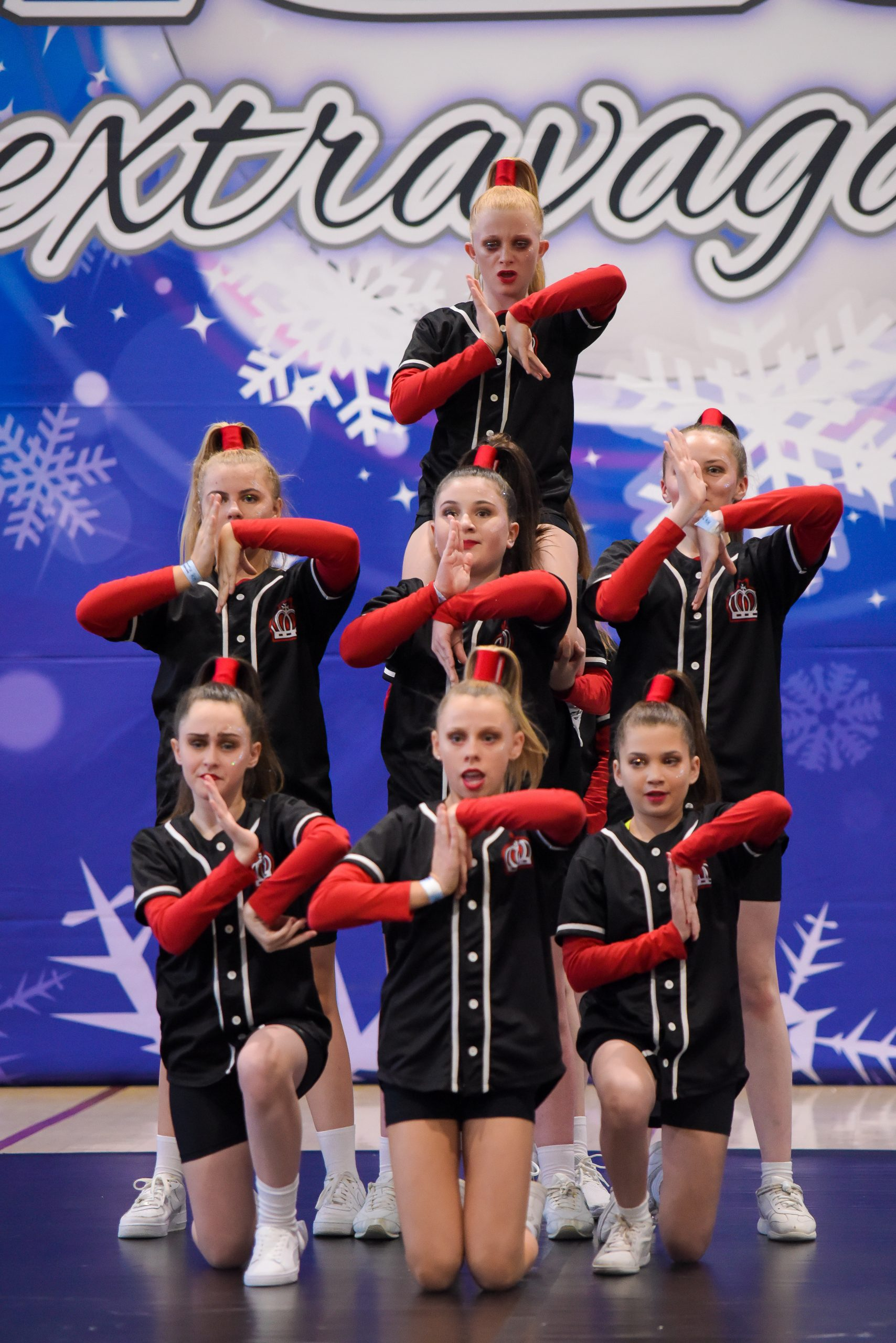 A hip hop team dressed in black and red compete on a dance floor