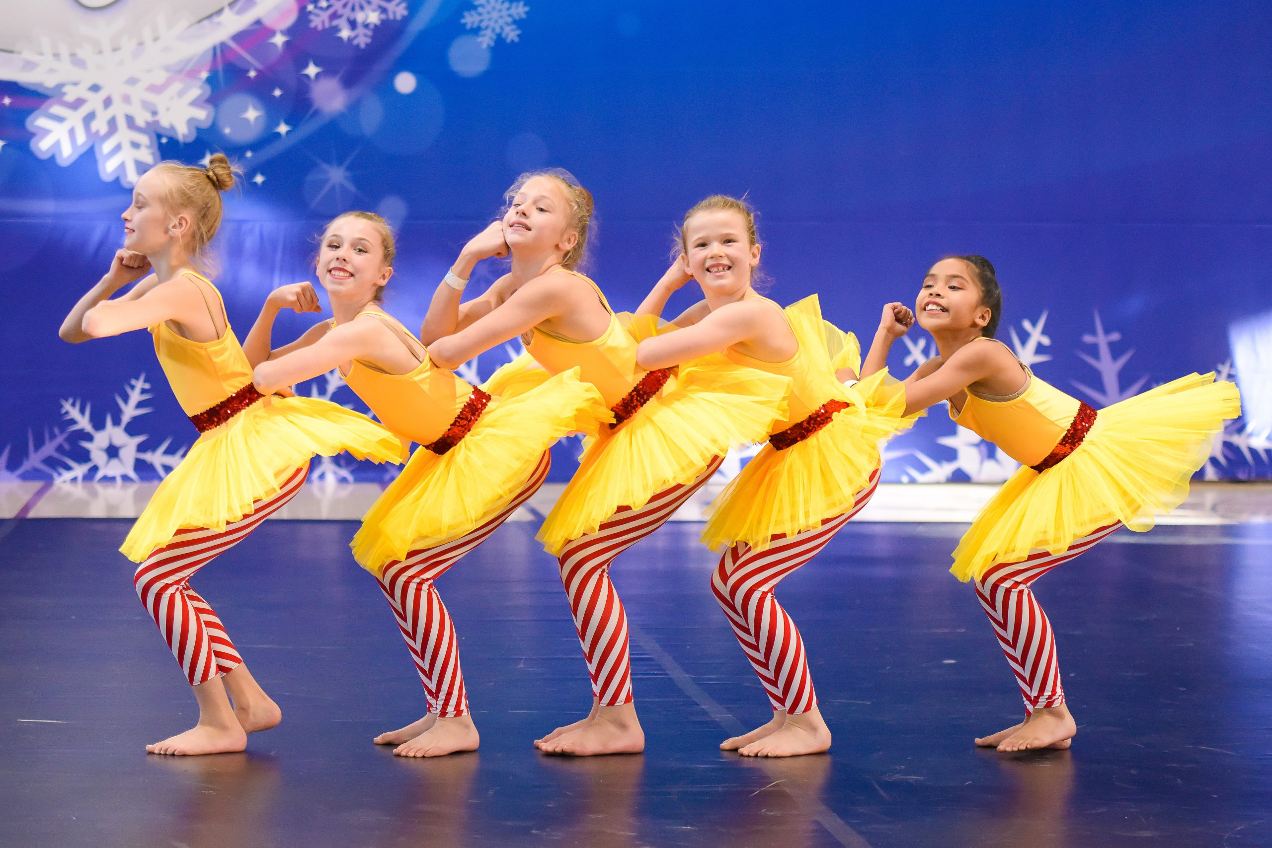 A dance team dressed in yellow, white and red take part in an ICE competition