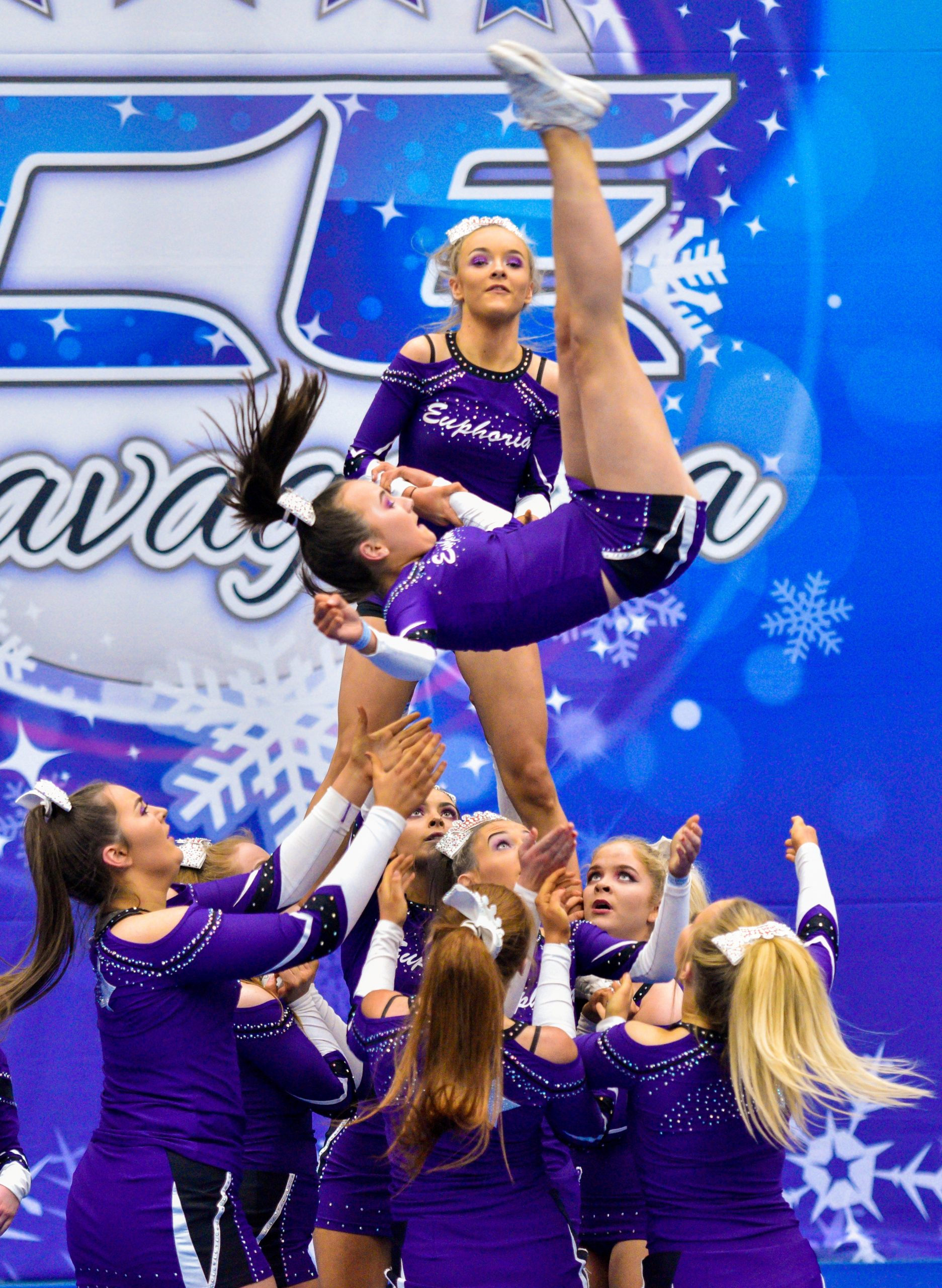 A cheer team dressed in purple compete in a pyramid at Incredibly Cool Events