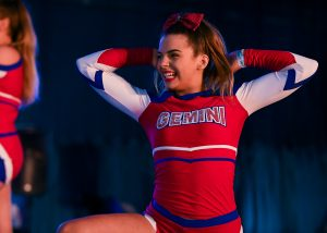A cheer athlete dressed in red, white and blue competes at ICE Championships